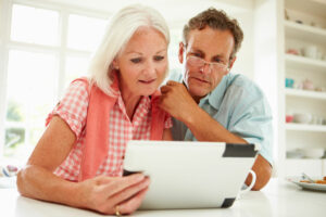 Man and woman sharing tablet to read.