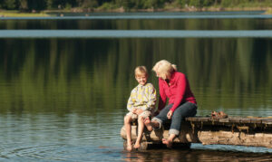 A child and woman sit on the dock on Lower Stillwater Lake - photo by Travel Montana